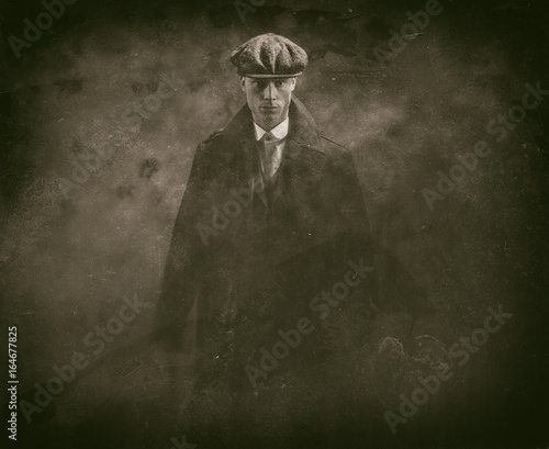 Antique wet plate photo of threatening 1920s english gangster holding gun in smoky room.