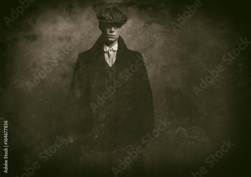 Antique wet plate photo of mysterious 1920s english gangster with flat cap and black coat.