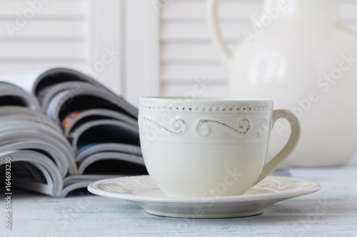 Stack of magazines and white cup of coffee on white background. Poster