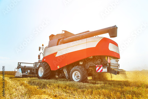 Close up The work of a combine harvester on a wheat field on a sunny day © yanik88