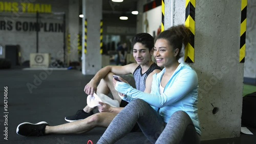 Young fit couple in gym resting, watching pictures in smartphone.