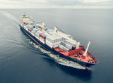 Aerial view of container vessel sailing in open sea - 164704651