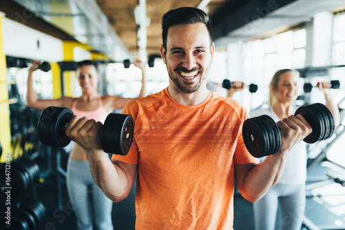 Group of friends exercising together in gym