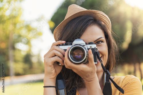 Fototapeta Smiling young woman using a camera to take photo.