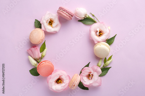 Foto op Aluminium Macarons Macarons and flowers wreath on a purple background. Colorful french dessert with fresh flowers. Top view