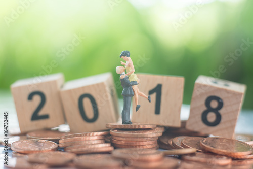 Poster The man pick the woman up with love and happiness on the pile of coins and wooden number 2018 background using as growing together, teamwork, partnership and achievement concept
