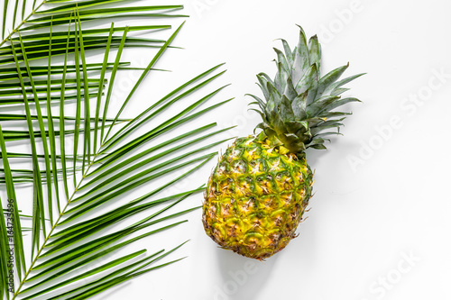 Foto Murales Pineapple and palm branch on white background top view copyspace