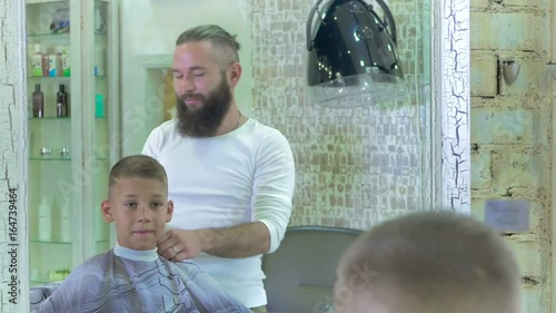 The hairdresser made a stylish haircut for a little boy in barber shop