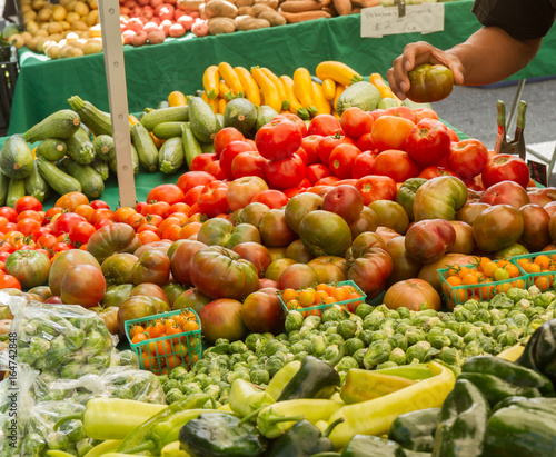 Farmer's market produce for sale at stand, with person holding an heirloom tomato. Cherry tomatoes, brussel sprouts, zucchini, squashes, gypsy peppers and bell peppers are visible.