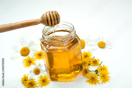 Still life of fresh honey and flowers