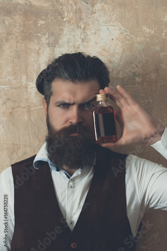 Hipster posing with bottle of red liqueur