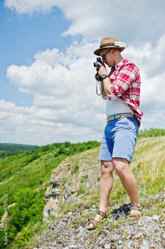 Poster Portrait of a stunning man in casual clothing with a hat posing with an old camera on the rock with a lake on the background