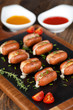 Mini sausages stuffed with cheese and baked on wooden background