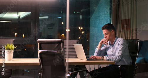 man working on laptop in dark office - 164778461