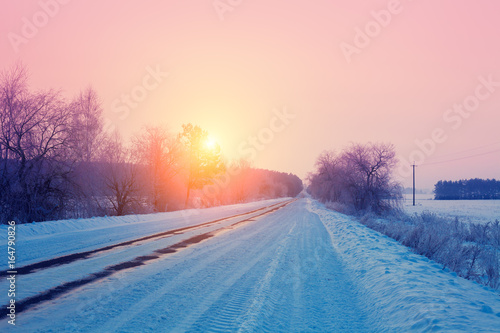 Foto op Aluminium Lichtroze Rural winter landscape. Sunrise over snowy road