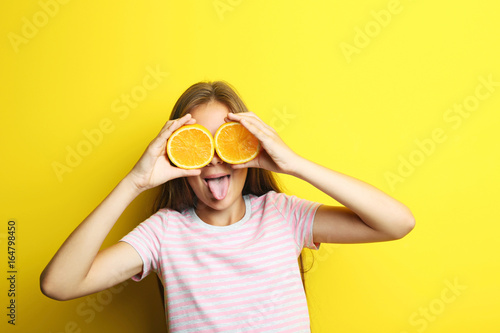 Portrait of beautiful girl with orange fruit on yellow background Poster