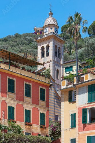 Portofino typical colorful houses and Divo Martino church bell tower with palm tree, Italy