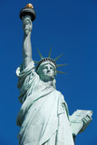 Statue of Liberty, sunlight and clear blue sky in New York