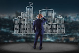 Businessman in front of a wall with Hand drawn city center displayed on a futuristic interface - Travel concept
