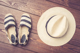 Straw hat and espadrilles on wooden background. Top view