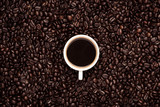 Coffee cup top view on roasted coffee beans background