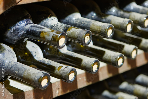 stacked old wine bottles in wine cellar