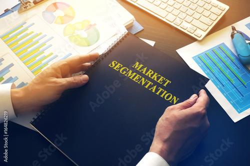 Marketologist taking book with name market segmentation.