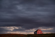 Dark clouds at dusk surround small house on horizon.