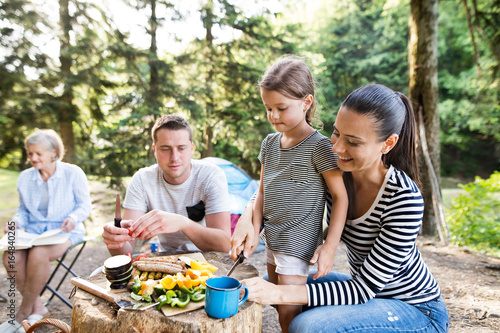 Beautiful family camping in forest, eating together. - 164840265