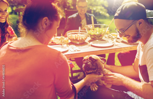 happy friends having dinner at summer garden party - 164856835