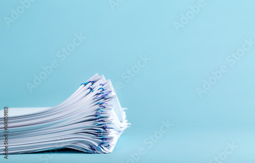 Pile of papers organized with paper clips on a blue background