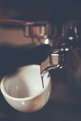 Professional espresso machine brewing a coffee. Coffee pouring into shot glasses.color vintage style .Thailand
