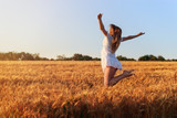 Beautiful young girl in white dress jumping in  wheat field - 164877234