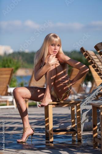Poster Beautiful topless blonde female model in fancy shoes and golden bikini sunbathin