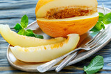 Dish with ripe yellow melon and cutlery.