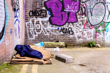 A sleeping bag and cardboard boxes on the ground in an alleyway behind an office block, used by a homeless person to sleep. © Stephen