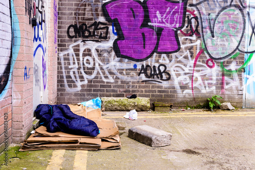 A sleeping bag and cardboard boxes on the ground in an alleyway behind an office block, used by a homeless person to sleep Poster