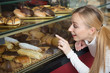 Young blond girl gladly selecting pastry