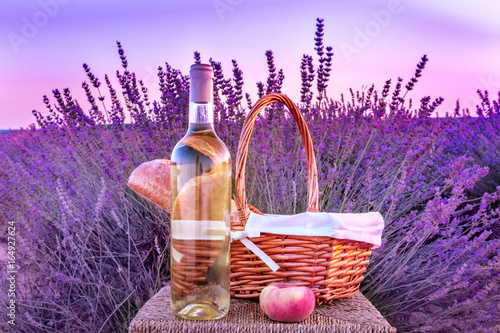 Bottle of white wine and picnic basket in lavender field