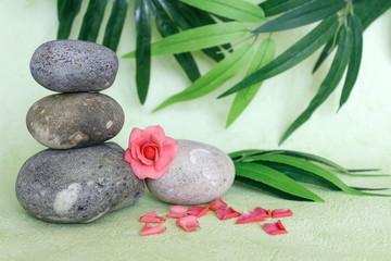Des galets décoratif empilés à la façon zen sur une planche de bois bamboo avec une fleur rose et une orchidée sur fond vert et feuillage