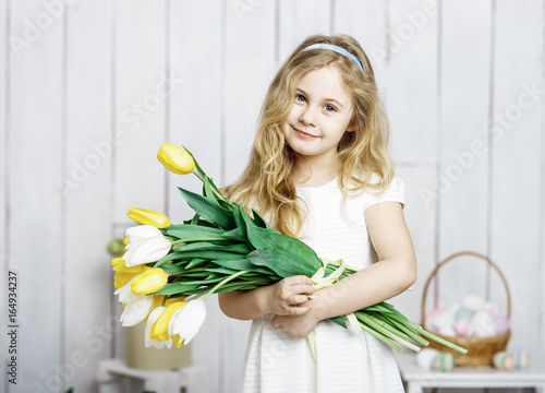 Portrait of cheerful little blonde girl with tulips bouquet on w