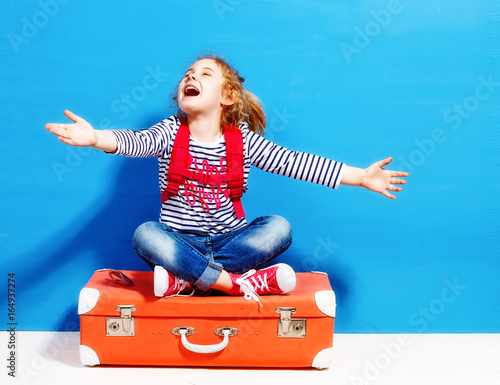 Child blonde girl with pink vintage suitcase ready for summer va