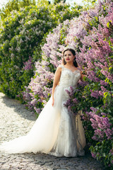 Full-length view of the stylishly dressed bride looking aside while standing near blooming liliac trees in Prague.