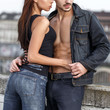 Young woman touching boyfriends abs in city