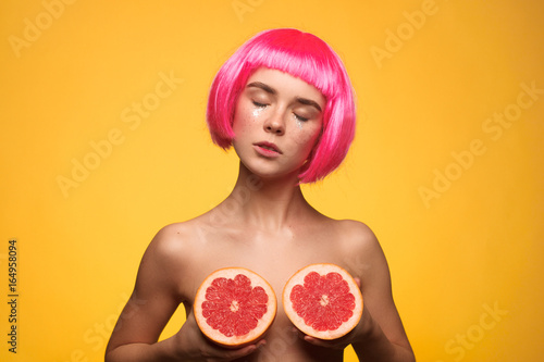 Poster Sensual model covering breast with fruit