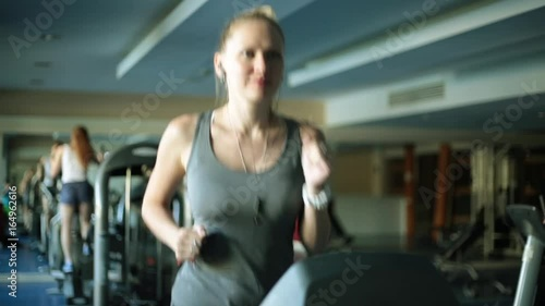 Attractive woman on a treadmill. Girl is running in the fitness club. © dubchikov