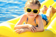 Leinwandbild Motiv Little girl in sunglasses swimming on inflatable beach mattress.