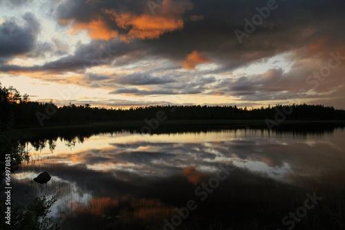 See in Schweden mit angestrahlten Wolken am Abendhimmel