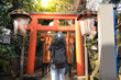 Tourist backpacker is sightseeing while travel in Ueno Park Torii shine in Tokyo, Japan.