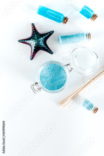 Dead sea cosmetics. Sea salt, blue clay and lotion on white background top view copyspace